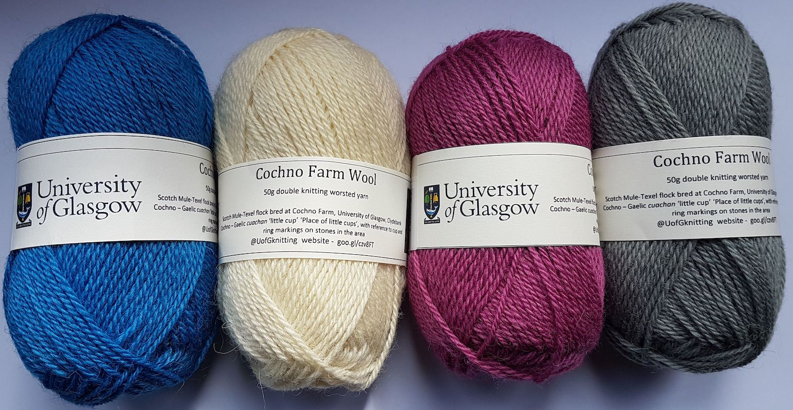 Colour photograph showing balls of Cochno wool in 4 colours – University Blue, Natural, Thistle Pink and Slate Grey (copyright University of Glasgow)